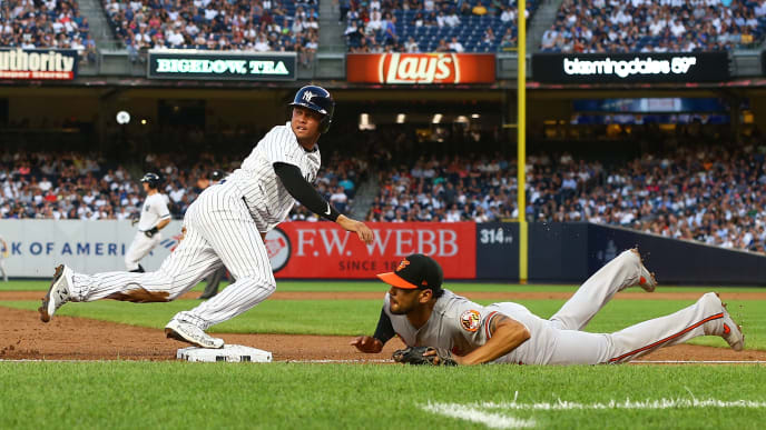 NEW YORK, NEW YORK - AUGUST 12:  Breyvic Valera #70 of the New York Yankees scores on a throwing error by catcher Chance Sisco #15 of the Baltimore Orioles in the second inning at Yankee Stadium on August 12, 2019 in New York City. (Photo by Mike Stobe/Getty Images)