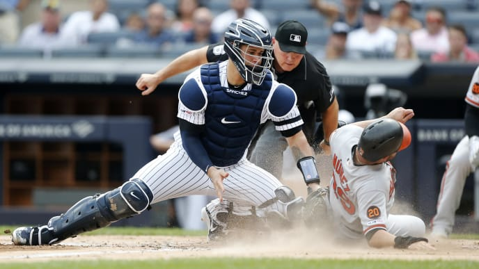 NEW YORK, NEW YORK - AUGUST 14:   Renato Nunez #39 of the Baltimore Orioles beats the tag from Gary Sanchez #24 of the New York Yankees to score a run in the third inning at Yankee Stadium on August 14, 2019 in New York City. (Photo by Jim McIsaac/Getty Images)