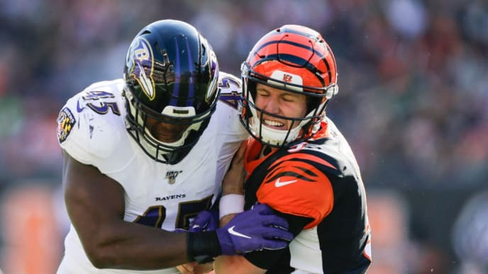 CINCINNATI, OHIO - NOVEMBER 10: Ryan Finley #5 of the Cincinnati Bengals is tackled by Jaylon Ferguson #45 of the Baltimore Ravens during the second quarter of the game at Paul Brown Stadium on November 10, 2019 in Cincinnati, Ohio. (Photo by Silas Walker/Getty Images)