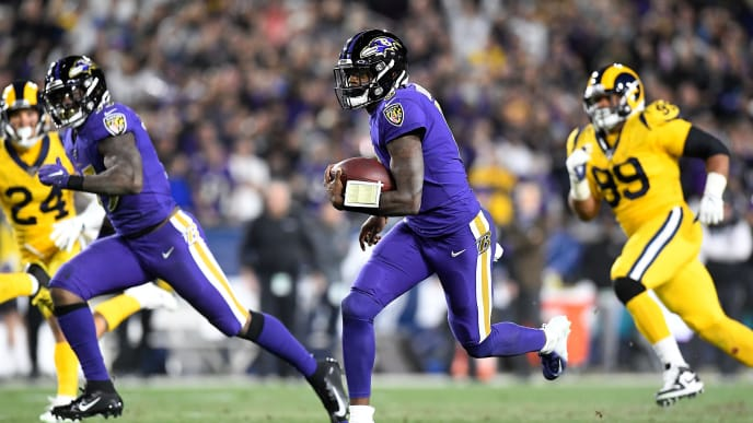 LOS ANGELES, CALIFORNIA - NOVEMBER 25:  Quarterback Lamar Jackson #8 of the Baltimore Ravens carries the ball against the defense of the Los Angeles Rams at Los Angeles Memorial Coliseum on November 25, 2019 in Los Angeles, California. (Photo by Kevork Djansezian/Getty Images)
