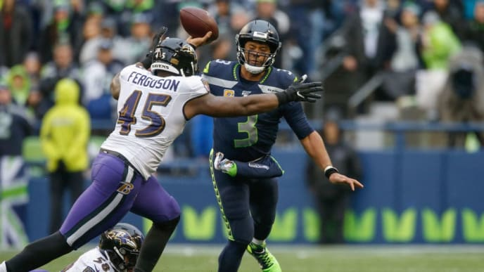 SEATTLE, WA - OCTOBER 20:  Quarterback Russell Wilson #3 of the Seattle Seahawks passes under pressure from linebacker Jaylon Ferguson #45 of the Baltimore Ravens at CenturyLink Field on October 20, 2019 in Seattle, Washington.  (Photo by Otto Greule Jr/Getty Images)