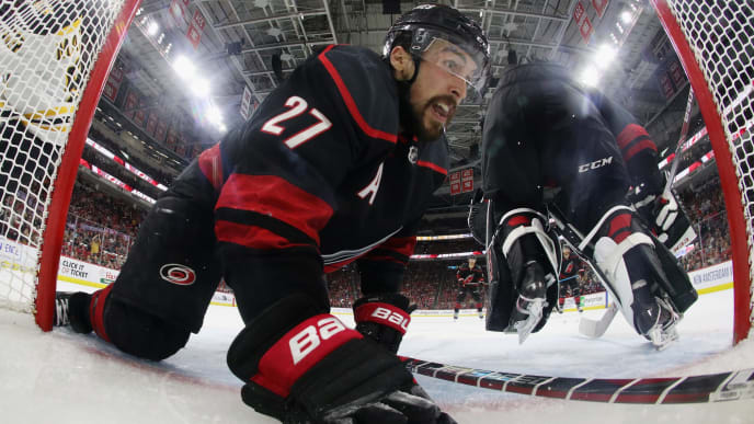 RALEIGH, NORTH CAROLINA - MAY 16: Justin Faulk #27 of the Carolina Hurricanes slides into the net during the third period against the Boston Bruins in Game Four of the Eastern Conference Final during the 2019 NHL Stanley Cup Playoffs at the PNC Arena on May 16, 2019 in Raleigh, North Carolina. The Bruins defeated the Hurricanes 4-0 to move on to the Stanley Cup Finals. (Photo by Bruce Bennett/Getty Images)