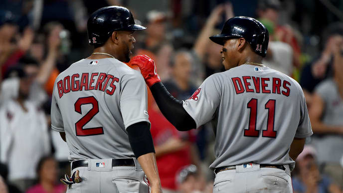 BALTIMORE, MD - JULY 20: Xander Bogaerts #2 and Rafael Devers #11 of the Boston Red Sox celebrate after scoring during the fourth inning against the Baltimore Orioles at Oriole Park at Camden Yards on July 20, 2019 in Baltimore, Maryland. (Photo by Will Newton/Getty Images)
