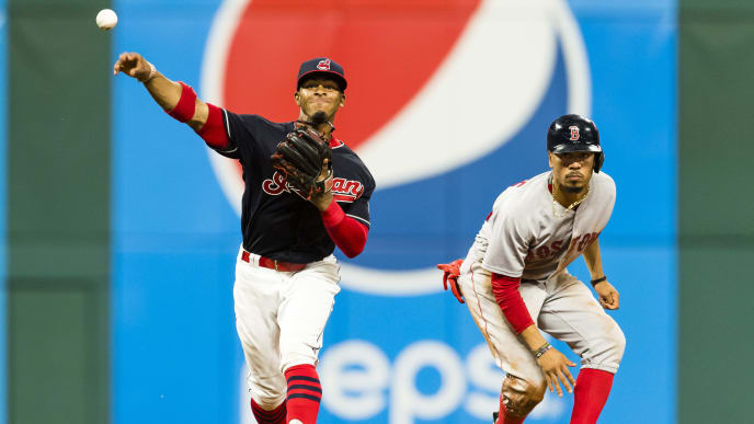 CLEVELAND, OH - AUGUST 21: Shortstop Francisco Lindor #12 of the Cleveland Indians throws to first as Mookie Betts #50 of the Boston Red Sox is out at second base during the seventh inning at Progressive Field on August 21, 2017 in Cleveland, Ohio. (Photo by Jason Miller/Getty Images)