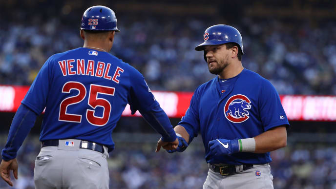 LOS ANGELES, CALIFORNIA - JUNE 15: Kyle Schwarber #12 of the Chicago Cubs gets a fist bump from first base coach Will Venable #25 after Schwarber singled to right field in the sixth inning of the MLB game against the Los Angeles Dodgers at Dodger Stadium on June 15, 2019 in Los Angeles, California. The Cubs defeated the Dodgers 2-1. (Photo by Victor Decolongon/Getty Images)