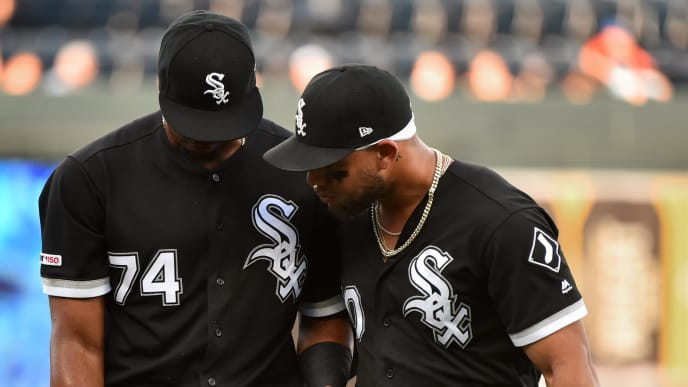 KANSAS CITY, MISSOURI - JULY 16:  Eloy Jimenez #74 of the Chicago White Sox is helped off the field by Yoan Moncada #10 after he collided with center fielder Charlie Tilson #22 while attempting to catch a ball hit by Whit Merrifield of the Kansas City Royals in the first inning at Kauffman Stadium on July 16, 2019 in Kansas City, Missouri. (Photo by Ed Zurga/Getty Images)