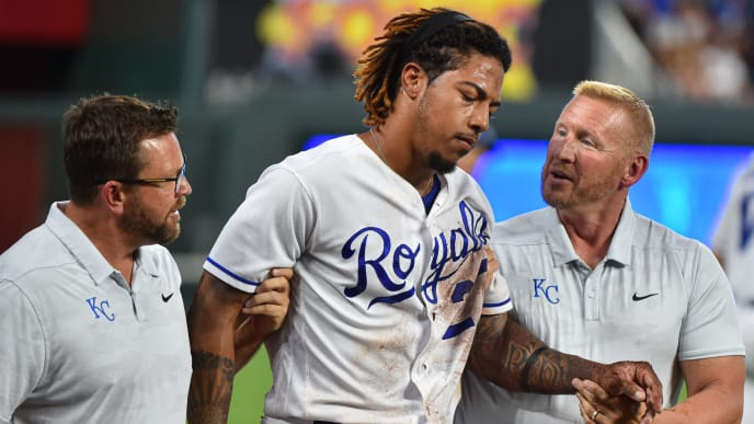 KANSAS CITY, MISSOURI - JULY 16:  Adalberto Mondesi #27 of the Kansas City Royals is helped off the field by a team trainers after he was injured while trying to catch a foul ball hit by Yolmer Sanchez #5 of the Chicago White Sox in the fifth inning at Kauffman Stadium on July 16, 2019 in Kansas City, Missouri. (Photo by Ed Zurga/Getty Images)