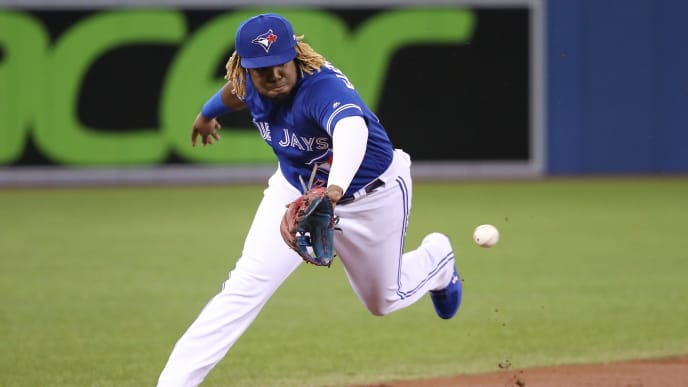 TORONTO, ON - MAY 11: Vladimir Guerrero Jr. #27 of the Toronto Blue Jays makes a defensive play and throws out the baserunner in the first inning during MLB game action against the Chicago White Sox at Rogers Centre on May 11, 2019 in Toronto, Canada. (Photo by Tom Szczerbowski/Getty Images)