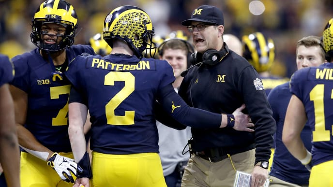 ATLANTA, GEORGIA - DECEMBER 29:  Shea Patterson #2 and head coach Jim Harbaugh of the Michigan Wolverines celebrate the first quarter touchdown against the Florida Gators during the Chick-fil-A Peach Bowl at Mercedes-Benz Stadium on December 29, 2018 in Atlanta, Georgia. (Photo by Joe Robbins/Getty Images)