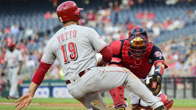 WASHINGTON, DC - AUGUST 12: Joey Votto #19 of the Cincinnati Reds is tagged out at home plate by Kurt Suzuki #28 of the Washington Nationals in the first inning at Nationals Park on August 12, 2019 in Washington, DC. (Photo by Patrick McDermott/Getty Images)