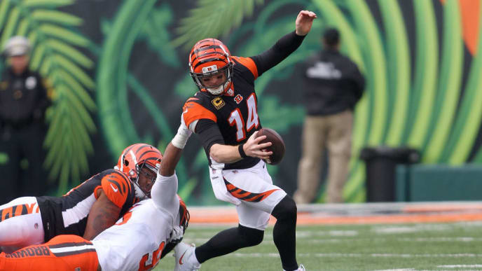 CINCINNATI, OH - NOVEMBER 25:  Andy Dalton #14 of the Cincinnati Bengals slips out of an attempted tackle by Myles Garrett #95 of the Cleveland Browns during the second quarter at Paul Brown Stadium on November 25, 2018 in Cincinnati, Ohio. (Photo by John Grieshop/Getty Images)