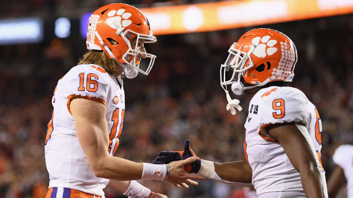SANTA CLARA, CA - JANUARY 07:  Trevor Lawrence #16 and Travis Etienne #9 of the Clemson Tigers celebrate their second quarter touchdown against the Alabama Crimson Tide in the CFP National Championship presented by AT&T at Levi's Stadium on January 7, 2019 in Santa Clara, California.  (Photo by Harry How/Getty Images)