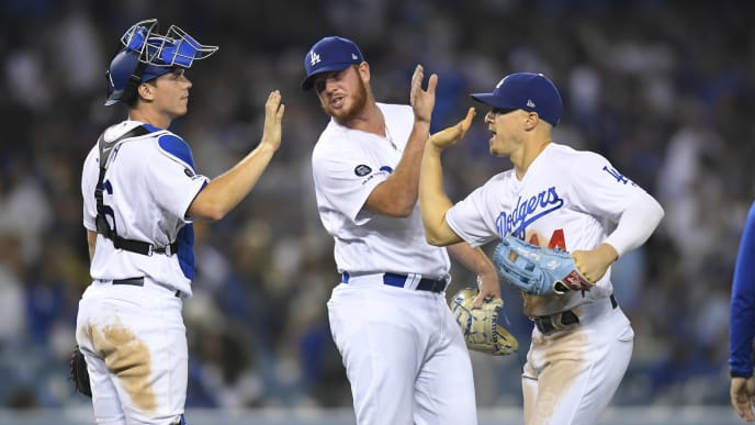 LOS ANGELES, CA - SEPTEMBER 20: Will Smith #16 of the Los Angeles Dodgers, Caleb Ferguson #64 and Enrique Hernandez #14 celebrate after the final out of the game in a 12-5 win over the Colorado Rockies at Dodger Stadium on September 20, 2019 in Los Angeles, California.  (Photo by John McCoy/Getty Images)