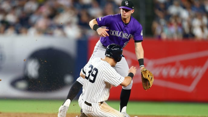 NEW YORK, NEW YORK - JULY 19: Mike Tauchman #39 of the New York Yankees steals second base as Trevor Story #27 of the Colorado Rockies is unable to catch a throwing error by Chris Iannetta #22 in the sixth inning at Yankee Stadium on July 19, 2019 in New York City. (Photo by Mike Stobe/Getty Images)