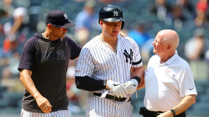 NEW YORK, NEW YORK - JULY 20: Aaron Boone #17 of the New York Yankees attends to Luke Voit #45 after being hit by a pitch in the fourth inning against the Colorado Rockies at Yankee Stadium on July 20, 2019 in New York City. (Photo by Mike Stobe/Getty Images)