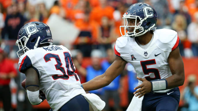 SYRACUSE, NY - SEPTEMBER 22:  David Pindell #5 of the Connecticut Huskies hands the ball off to Kevin Mensah #34 against the Syracuse Orange during the first quarter at the Carrier Dome on September 22, 2018 in Syracuse, New York. Syracuse defeated Connecticut 51-21. (Photo by Rich Barnes/Getty Images)