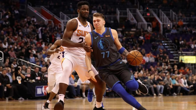 PHOENIX, ARIZONA - DECEMBER 13:  Luka Doncic #77 of the Dallas Mavericks drives the ball past Deandre Ayton #22 of the Phoenix Suns during the NBA game at Talking Stick Resort Arena on December 13, 2018 in Phoenix, Arizona.  The Suns defeated the Mavericks 99-89.  NOTE TO USER: User expressly acknowledges and agrees that, by downloading and or using this photograph, User is consenting to the terms and conditions of the Getty Images License Agreement. (Photo by Christian Petersen/Getty Images)