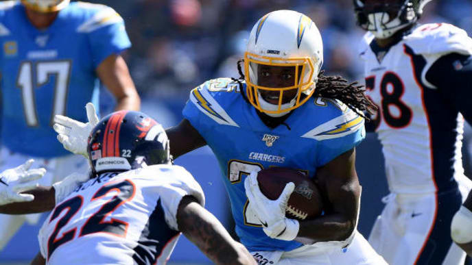 CARSON, CALIFORNIA - OCTOBER 06:  Melvin Gordon #25 of the Los Angeles Chargers cuts back on Kareem Jackson #22 and Isaac Yiadom #26 of the Denver Broncos during the second quarter at Dignity Health Sports Park on October 06, 2019 in Carson, California. (Photo by Harry How/Getty Images)
