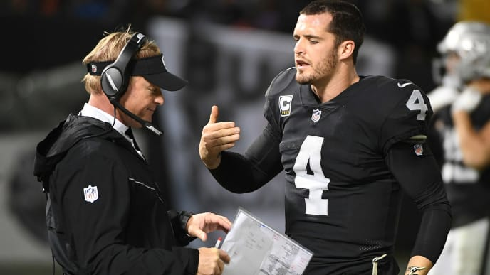 OAKLAND, CA - DECEMBER 24: Derek Carr #4 of the Oakland Raiders speaks with head coach Jon Gruden on the sidelines during their NFL game against the Denver Broncos at Oakland-Alameda County Coliseum on December 24, 2018 in Oakland, California. (Photo by Robert Reiners/Getty Images)