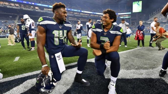 SEATTLE, WASHINGTON - AUGUST 08: D.K. Metcalf #14 and Russell Wilson #3 of the Seattle Seahawks have a chat after the preseason game victory over the Denver Broncos at CenturyLink Field on August 08, 2019 in Seattle, Washington. (Photo by Alika Jenner/Getty Images)