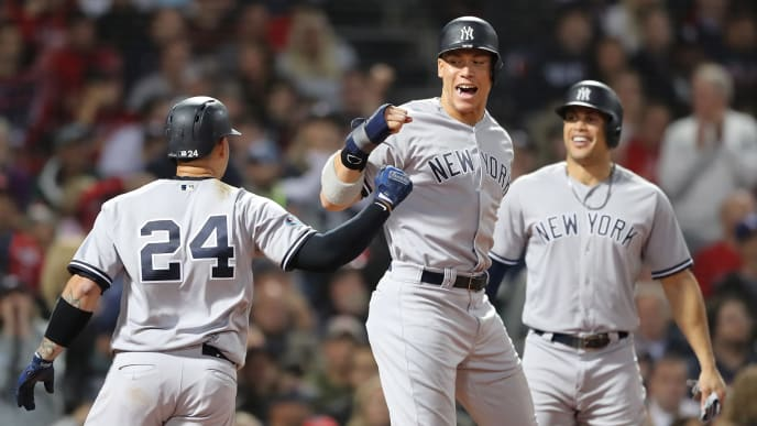 BOSTON, MA - OCTOBER 06:  Gary Sanchez #24 and Aaron Judge #99 of the New York Yankees celebrate after Sanchez hit a three-run home run as teammate Giancarlo Stanton #27 watches during the seventh inning of Game Two of the American League Division Series against the Boston Red Sox at Fenway Park on October 6, 2018 in Boston, Massachusetts.  (Photo by Elsa/Getty Images)