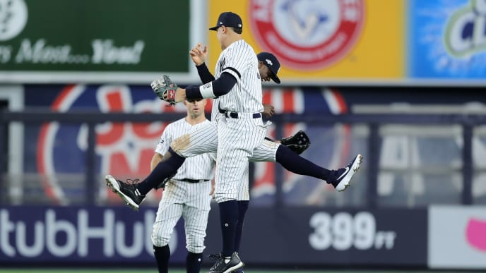 NEW YORK, NEW YORK - OCTOBER 05: Aaron Judge #99 and Cameron Maybin #38 of the New York Yankees celebrate their 8-2 win over the Minnesota Twins in game two of the American League Division Series at Yankee Stadium on October 05, 2019 in New York City. (Photo by Elsa/Getty Images)