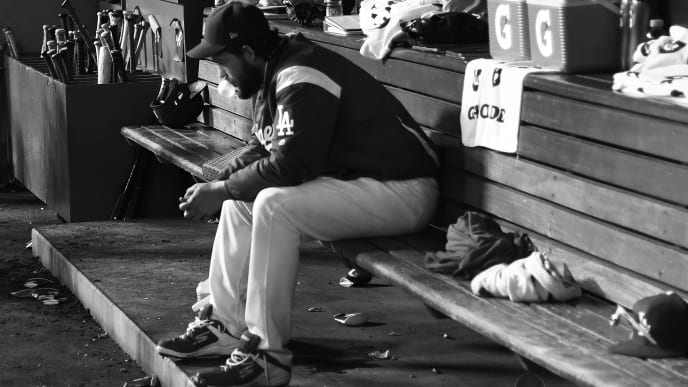 LOS ANGELES, CALIFORNIA - OCTOBER 09: (EDITOR'S NOTE: This iage has been converted to black and white) Clayton Kershaw #22 of the Los Angeles Dodgers sits in the dug out after leaving the game and giving up back to back home runs in the eighth inning during game five of the National League Division Series against the Washington Nationals at Dodger Stadium on October 09, 2019 in Los Angeles, California. (Photo by Harry How/Getty Images)