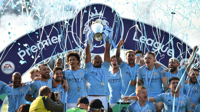 Manchester City's Belgian defender Vincent Kompany (C) holds up the Premier League trophy after their 4-1 victory in the English Premier League football match between Brighton and Hove Albion and Manchester City at the American Express Community Stadium in Brighton, southern England on May 12, 2019. - Manchester City held off a titanic challenge from Liverpool to become the first side in a decade to retain the Premier League on Sunday by coming from behind to beat Brighton 4-1 on Sunday. (Photo by Glyn KIRK / AFP) / RESTRICTED TO EDITORIAL USE. No use with unauthorized audio, video, data, fixture lists, club/league logos or 'live' services. Online in-match use limited to 120 images. An additional 40 images may be used in extra time. No video emulation. Social media in-match use limited to 120 images. An additional 40 images may be used in extra time. No use in betting publications, games or single club/league/player publications. /         (Photo credit should read GLYN KIRK/AFP/Getty Images)