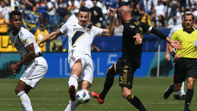 Zlatan Ibrahimovic from LA Galaxy (C) is tackled by Laurent Ciman (R)  of LAFC during their Major League Soccer (MLS) game at the StarHub Center in Los Angeles, California, on March 31, 2018. LA Galaxy went on to win 4-3 with two goals from Ibrahimovic.    / AFP PHOTO / Mark RALSTON        (Photo credit should read MARK RALSTON/AFP/Getty Images)
