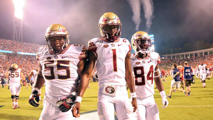 CHARLOTTESVILLE, VA - SEPTEMBER 14: James Blackman #1 of the Florida State Seminoles walks off the field between Dontae Lucas #55 and Adarius Dent #84 after the end of a game against the Virginia Cavaliers at Scott Stadium on September 14, 2019 in Charlottesville, Virginia. (Photo by Ryan M. Kelly/Getty Images)