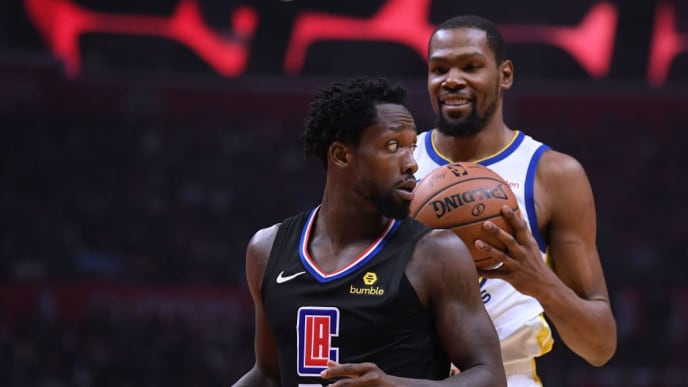 LOS ANGELES, CALIFORNIA - APRIL 18:  Patrick Beverley #21 of the LA Clippers looks back at a smiling Kevin Durant #35 of the Golden State Warriors during Game Two of Round One of the 2019 NBA Playoffs at Staples Center on April 18, 2019 in Los Angeles, California. (Photo by Harry How/Getty Images)  NOTE TO USER: User expressly acknowledges and agrees that, by downloading and or using this photograph, User is consenting to the terms and conditions of the Getty Images License Agreement.