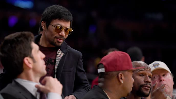 LOS ANGELES, CALIFORNIA - JANUARY 21:  Manny Pacquiao greets Floyd Mayweather Jr. as he passes by during the game between the Golden State Warriors and the Los Angeles Lakers at Staples Center on January 21, 2019 in Los Angeles, California.  NOTE TO USER: User expressly acknowledges and agrees that, by downloading and or using this photograph, User is consenting to the terms and conditions of the Getty Images License Agreement. (Photo by Harry How/Getty Images)