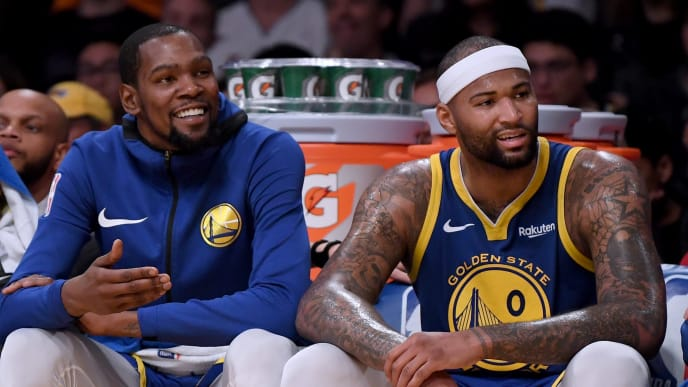 LOS ANGELES, CALIFORNIA - JANUARY 21:  Stephen Curry #30, Kevin Durant #35 and DeMarcus Cousins #0 of the Golden State Warriors laugh on the bench during a 130-111 win over the Los Angeles Lakers at Staples Center on January 21, 2019 in Los Angeles, California.  NOTE TO USER: User expressly acknowledges and agrees that, by downloading and or using this photograph, User is consenting to the terms and conditions of the Getty Images License Agreement. (Photo by Harry How/Getty Images)