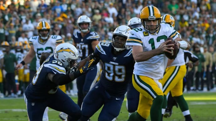CARSON, CA - NOVEMBER 03: Aaron Rodgers #12 of the Green Bay Packers scrambles past Thomas Davis #58 and Jerry Tillery #99 of the Los Angeles Chargers for a two-point conversion in the fourth quarter at Dignity Health Sports Park on November 3, 2019 in Carson, California. (Photo by John McCoy/Getty Images) Chargers won 26-11.