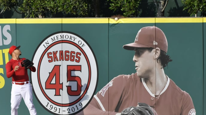ANAHEIM, CA - SEPTEMBER 27: Hansel Robles #57 of the Los Angeles Angels looks at a ball as it goes over the wall and a photo of Tyler Skaggs #45 during batting practice before playing the Houston Astros at Angel Stadium of Anaheim on September 27, 2019 in Anaheim, California. (Photo by John McCoy/Getty Images)