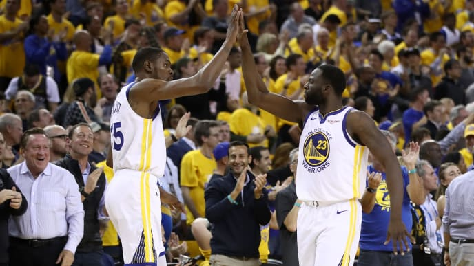 OAKLAND, CALIFORNIA - MAY 08:   Kevin Durant #35 of the Golden State Warriors high-fives Draymond Green #23 after the Warriors scored a basket against the Houston Rockets during Game Five of the Western Conference Semifinals of the 2019 NBA Playoffs at ORACLE Arena on May 08, 2019 in Oakland, California.  NOTE TO USER: User expressly acknowledges and agrees that, by downloading and or using this photograph, User is consenting to the terms and conditions of the Getty Images License Agreement.  (Photo by Ezra Shaw/Getty Images)