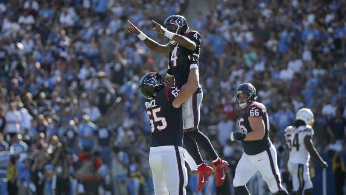 CARSON, CALIFORNIA - SEPTEMBER 22: Deshaun Watson #4 of the Houston Texans is hoisted up by Greg Mancz #65 after throwing for a touchdown in the fourth quarter against the Los Angeles Chargers at Dignity Health Sports Park on September 22, 2019 in Carson, California. The Texans defeated the Chargers 27-20. (Photo by Jeff Gross/Getty Images)