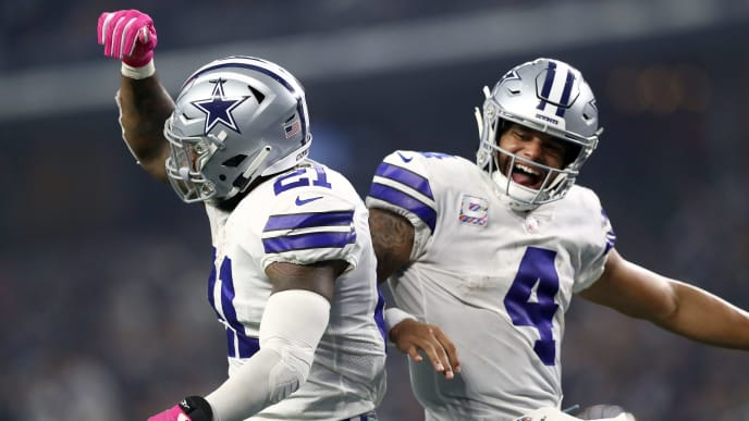 ARLINGTON, TX - OCTOBER 14:  Ezekiel Elliott #21 and Dak Prescott #4 of the Dallas Cowboys celebrate the fourth quarter touchdown against the Jacksonville Jaguars at AT&T Stadium on October 14, 2018 in Arlington, Texas.  (Photo by Ronald Martinez/Getty Images)
