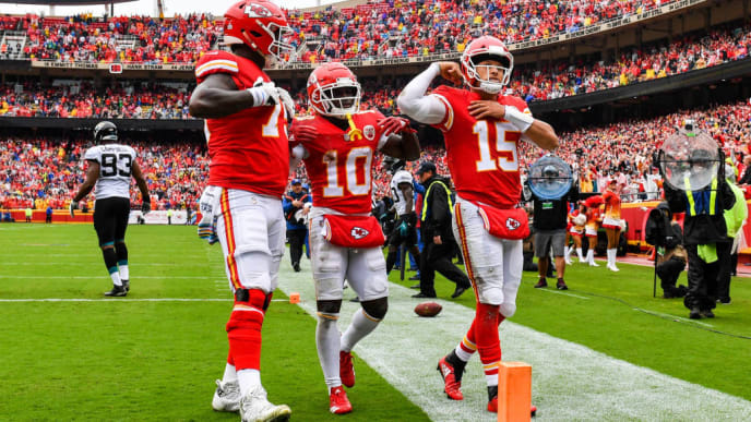 KANSAS CITY, MO - OCTOBER 7: Patrick Mahomes #15 of the Kansas City Chiefs flexes his muscle with teammates Tyreek Hill #10 and Cameron Erving #75 after scoring a rushing touchdown during the first quarter of the game against the Jacksonville Jaguars at Arrowhead Stadium on October 7, 2018 in Kansas City, Missouri. (Photo by Peter Aiken/Getty Images)