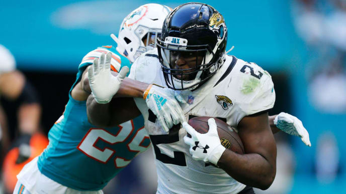 MIAMI, FLORIDA - DECEMBER 23:  Leonard Fournette #27 of the Jacksonville Jaguars tries to avoid the tackle of Minkah Fitzpatrick #29 of the Miami Dolphins in the second half at Hard Rock Stadium on December 23, 2018 in Miami, Florida. (Photo by Michael Reaves/Getty Images)