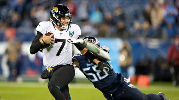 NASHVILLE, TN - NOVEMBER 24:  Nick Foles #7 of the Jacksonville Jaguars runs the ball and is tackled from behind by Harold Landry III #58 of the Tennessee Titans in the second half at Nissan Stadium on November 24, 2019 in Nashville, Tennessee.   The Titans defeated the Jaguars 42-20.  (Photo by Wesley Hitt/Getty Images)