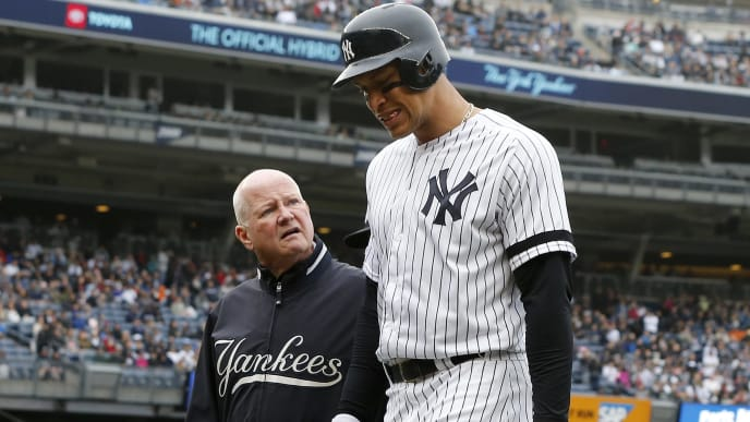 NEW YORK, NEW YORK - APRIL 20:   Aaron Judge #99 of the New York Yankees leaves a game in the sixth inning against the Kansas City Royals with trainer Steve Donohue at Yankee Stadium on April 20, 2019 in New York City. (Photo by Jim McIsaac/Getty Images)
