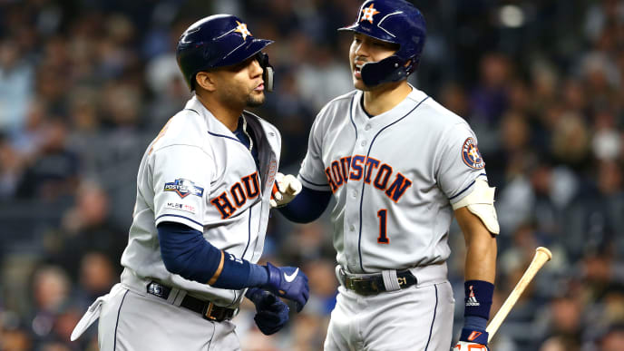 NEW YORK, NEW YORK - OCTOBER 15: Yuli Gurriel #10 celebrates with Carlos Correa #1 of the Houston Astros after hitting a sacrifice fly ball during the seventh inning against the New York Yankees in game three of the American League Championship Series at Yankee Stadium on October 15, 2019 in New York City. (Photo by Mike Stobe/Getty Images)