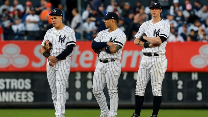 NEW YORK, NEW YORK - OCTOBER 15:  (NEW YORK DAILIES OUT)    (L-R) Gio Urshela #29, Gleyber Torres #25 and DJ LeMahieu #26 of the New York Yankees look on against the Houston Astros in game three of the American League Championship Series at Yankee Stadium on October 15, 2019 in New York City. The Astros defeated the Yankees 4-1. (Photo by Jim McIsaac/Getty Images)