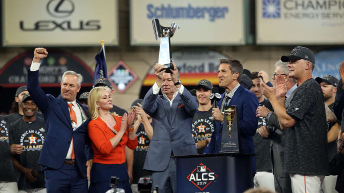HOUSTON, TEXAS - OCTOBER 19: Houston Astros owner Jim Crane lifts up the ALCS Championship Trophy as his wife Whitney, Reid Ryan, left and manager AJ Hinch look on after Game 6 of the American League Championship Series against the New York Yankees at Minute Maid Park on October 19, 2019 in Houston, Texas. (Photo by Bob Levey/Getty Images)