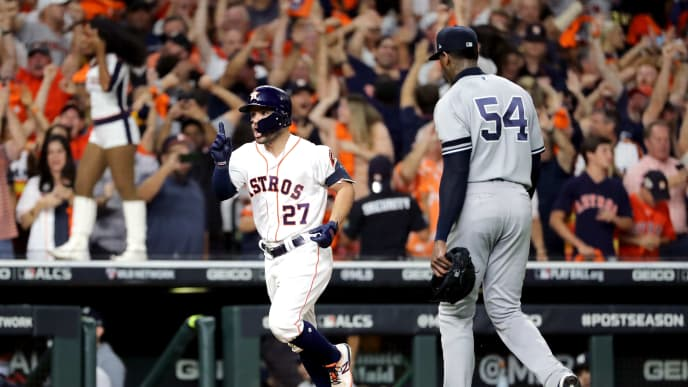 HOUSTON, TEXAS - OCTOBER 19:  Jose Altuve #27 of the Houston Astros comes home to score following his ninth inning walk-off two-run home run as Aroldis Chapman #54 of the New York Yankees walks off the field in game six of the American League Championship Series at Minute Maid Park on October 19, 2019 in Houston, Texas. The Astros defeated the Yankees 6-4. (Photo by Elsa/Getty Images)