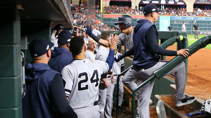 HOUSTON, TEXAS - OCTOBER 12:  Gio Urshela #29 of the New York Yankees is congratulated by his teammates after hitting a solo home run against the Houston Astros during the ninth inning in game one of the American League Championship Series at Minute Maid Park on October 12, 2019 in Houston, Texas. (Photo by Mike Ehrmann/Getty Images)