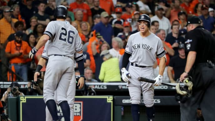HOUSTON, TEXAS - OCTOBER 19:  Aaron Judge #99 of the New York Yankees celebrates a game-tying two-run home run by DJ LeMahieu #26 against the Houston Astros during the ninth inning in game six of the American League Championship Series at Minute Maid Park on October 19, 2019 in Houston, Texas. (Photo by Elsa/Getty Images)