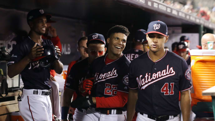 WASHINGTON, DC - OCTOBER 15: Juan Soto #22 of the Washington Nationals celebrates with teammates in the dugout after scoring in the first inning against the St. Louis Cardinals during game four of the National League Championship Series at Nationals Park on October 15, 2019 in Washington, DC. (Photo by Rob Carr/Getty Images)