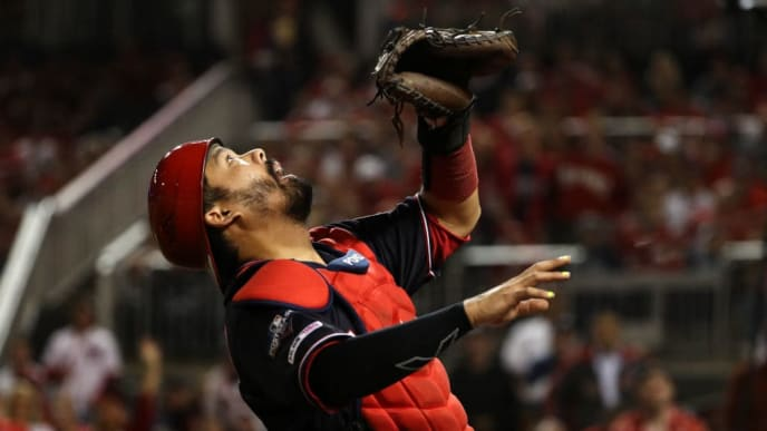 WASHINGTON, DC - OCTOBER 14: Catcher Kurt Suzuki #28 of the Washington Nationals makes a catch on Yadier Molina #4 of the St. Louis Cardinals during the second inning of game three of the National League Championship Series at Nationals Park on October 14, 2019 in Washington, DC. (Photo by Patrick Smith/Getty Images)